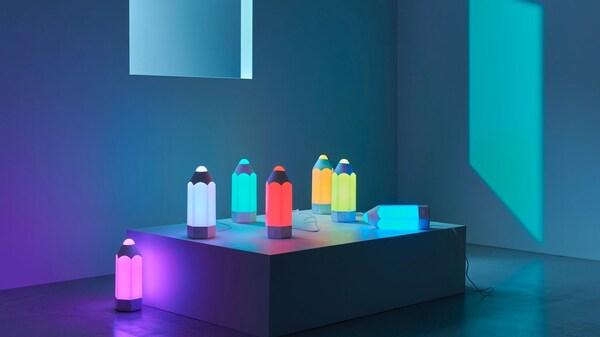 Meerdere PELARBOJ tafellampen in verschillende kleuren op een display in een kamer.