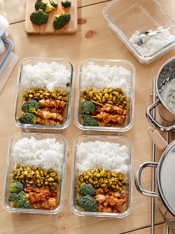 Mehrere IKEA 365+ Glasbehälter, gefüllt mit identischen Gerichten auf einer Arbeitsplatte.