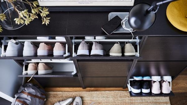 Mehrere Schuhschränke nebeneinander formen in einem Flur ein schmales Sideboard.