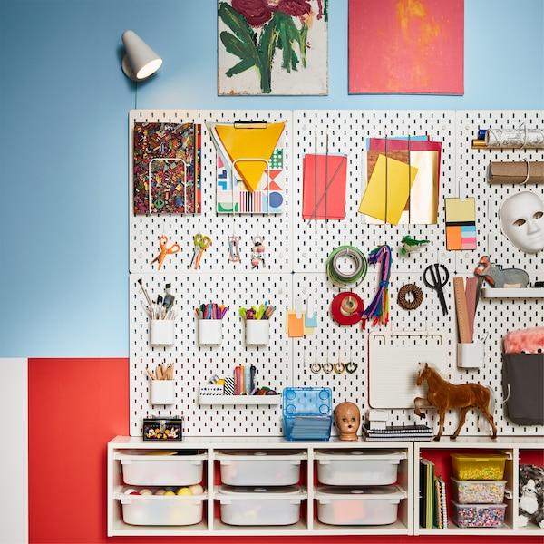 Mehrere SKÅDIS Lochplatten/Kombination in Weiß an einer bunten Zimmerwand. Daran sind viele Utensilien zu sehen.