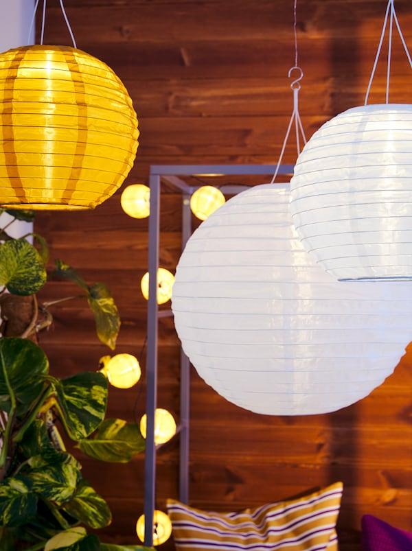 Mehrere SOLVINDEN Solarhängeleuchten hängen rund um eine SVANÖ Bank mit Rankgitter.