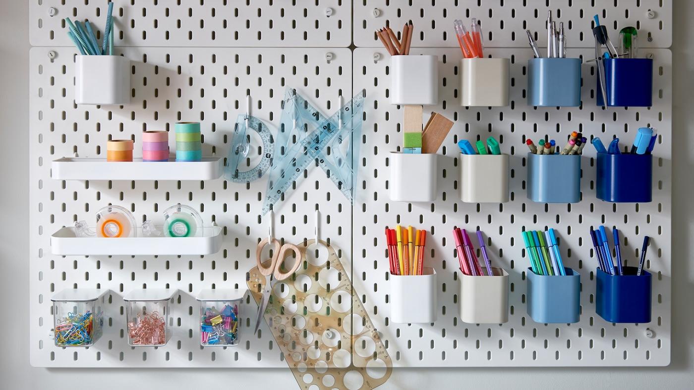 Mehrere weiße Lochplatten mit unterschiedlich farbigen Behältern, in denen bunte Stifte, Büroklammern und Klebeband aufbewahrt werden.