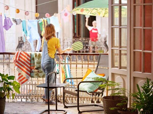 Meisje houdt een racket vast en leunt tegen een balkonreling. Verlichting en kleding hangt op de achtergrond.