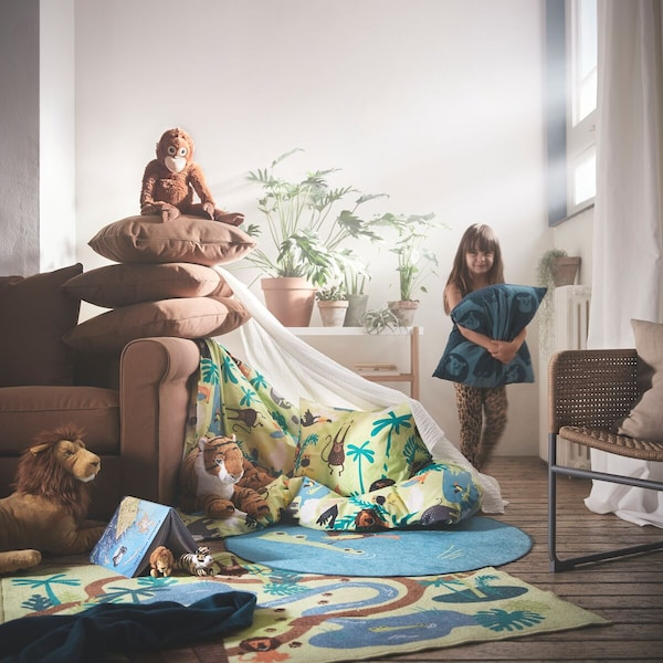 meisje is een nestje aan het bouwen met pluchen knuffels en dekens in de woonkamer