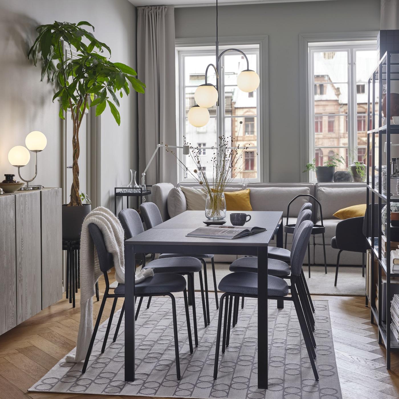 Meja berwarna hitam/coklat gelap dan kerusi berwarna kelabu terletak di atas ambal corak geometri. Di atasnya terdapat lampu pendan bersadur krom 3 lengan.