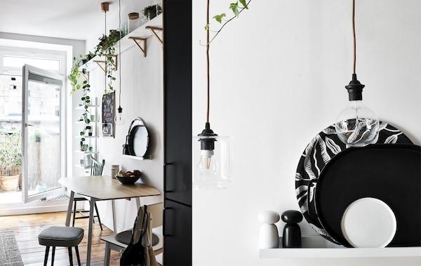 Meja dapur dan tumbuhan di atasnya yang berada di atas rak, dan gambar dulang hitam putih di atas rak dan mentol filamen yang diambil dari dekat.