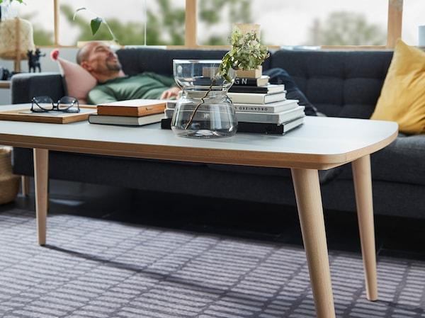 Meja kopi OMTÄNKSAM, dengan vas OMTÄNKSAM, buku dan cermin mata, berada dalam fokus. Seorang lelaki sedang berehat di atas sofa di bahagian belakang.
