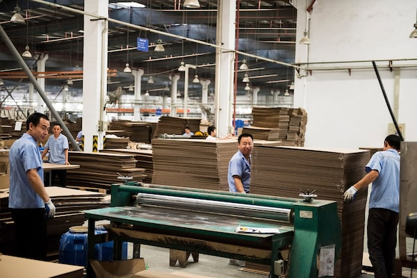 Men working inside an IKEA supplier factory, carefully working with stacks of thin wood surfaces.