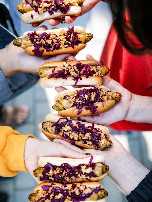 Menschen halten eine Kette von Veggie-Hotdogs in die Höhe
