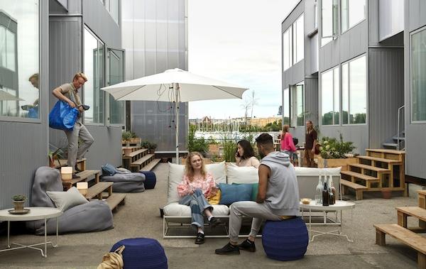 Menschen sitzen auf Sofas und Bodenkissen in einem Außenbereich zwischen Schiffscontainern. Auch ein Sonnenschirm und Beistelltische sind zu sehen.