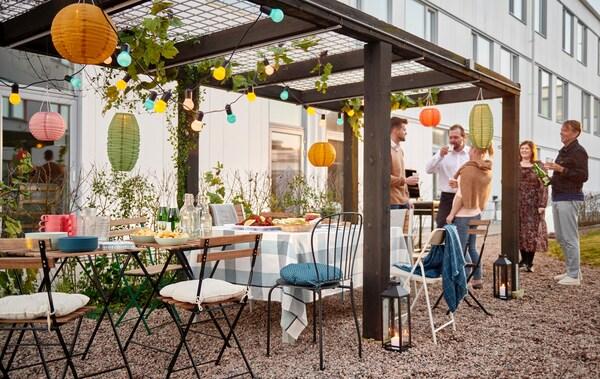 Menschen stehen im Freien an einem gedeckten Tisch mit vielen Solarleuchten