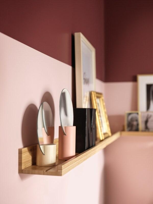 Mensola in bambù fissata ad una parete rosa. Sulla mensola cornici e vari oggetti decorativi.