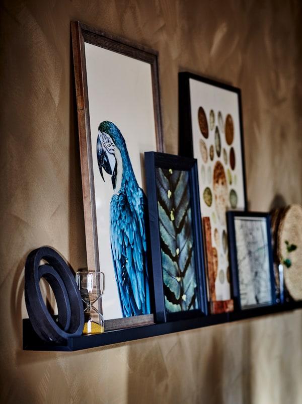 Mensola per quadri MOSSLANDA blu scuro con cornici e immagini nei toni del marrone, blu scuro e nero.