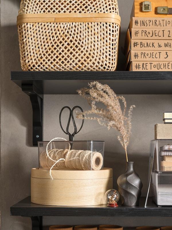 Mensole nere con scatola con coperchio SMARRA in bambù, contenitore con coperchio MALLGRODA rotondo, oggetti da lavoro e soprammobili.