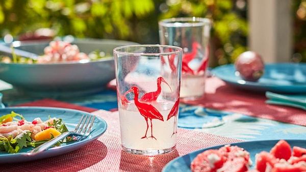 Mesa al aire libre iluminada por el sol con elementos de vajilla y cristalería con colores y estampados alegres y veraniegos. En los platos hay comida ligera.