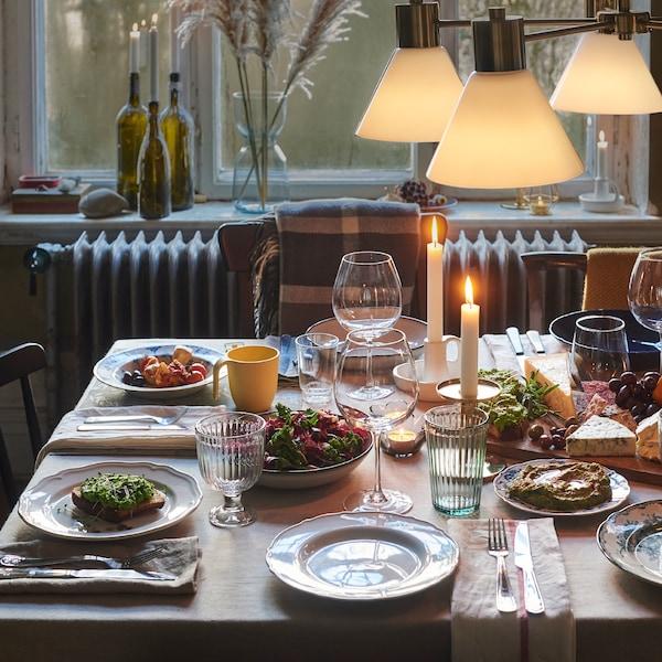 Mesa de comedor con mantel monocromático, trapos de cocina usados como servilletas y una mezcla desenfadada de platos y vasos.