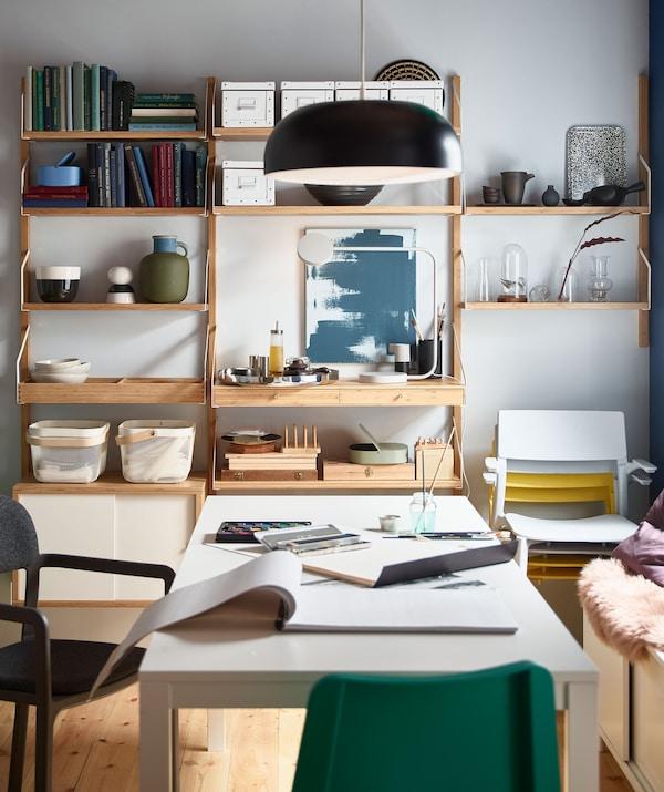 Mesa de comedor extensible EKEDALEN preparada para pintar con acuarelas cun estante SVALNÄS ao fondo.