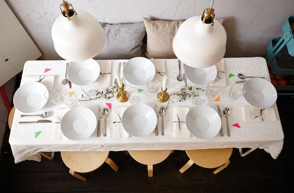 Mesa de comedor preparada con platos y cubiertos.