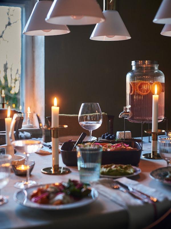 Mesa de comedor preparada para una comida informal con portavelas, un dispensador de bebidas, ollas y una bandeja para horno con exquisita comida.