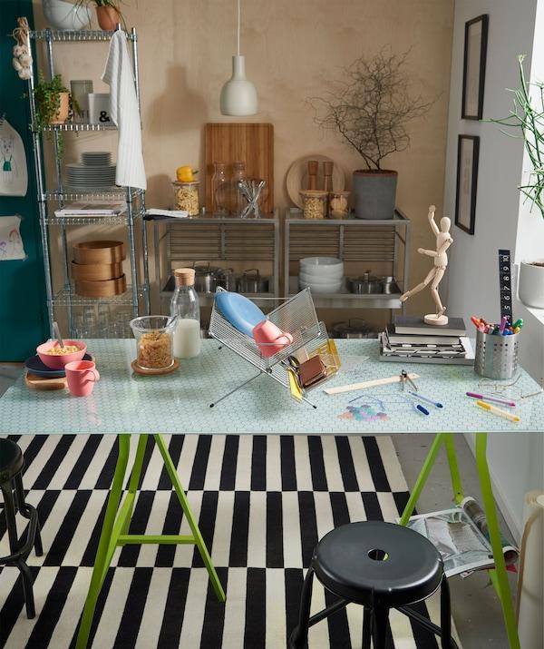 Mesa de cozinha com tampo em vidro, com um escorredor a servir de divisória entre as duas metades, uma para comer e outra com trabalho criativo em curso.