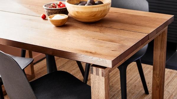 Mesa de madeira MÖRBYLÅNGA em castanho claro com variações na superfície e na cor de carvalho natural, combinada com cadeiras modernas e escuras.