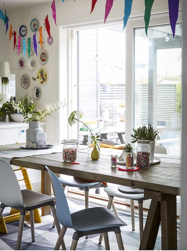 Mesa de refeição em madeira com tiras de pano coloridas