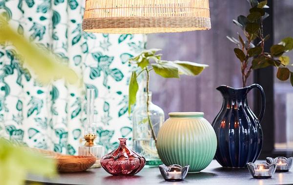 Mesa delicadamente decorada com pequenas jarras, velas e algumas folhas verdes, a fazer lembrar a primavera.
