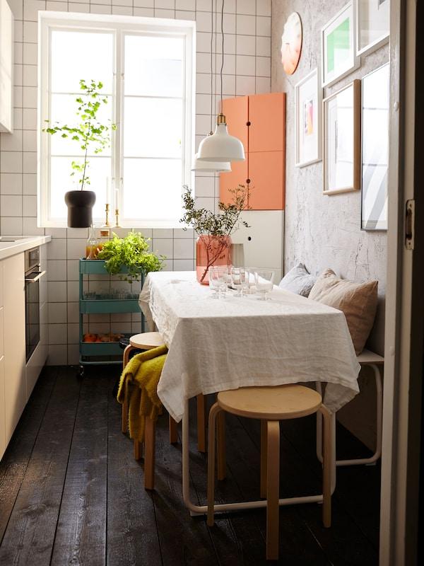 Mesa en una cocina pequeña con taburetes y un banco.