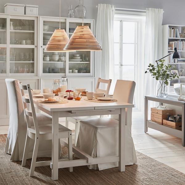 Mesa extensível e cadeiras NORDVIKEN numa mesa de pequeno almoço preparada. Os candeeiros suspensos acesos oferecem uma luz acolhedora.