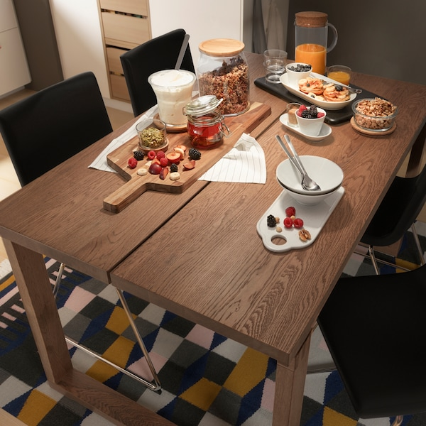 Mesa MÖRBYLÅNGA fabricada en chapa de roble sobre una alfombra. Sobre la mesa se ve una gran variedad de alimentos y utensilios de cocina.