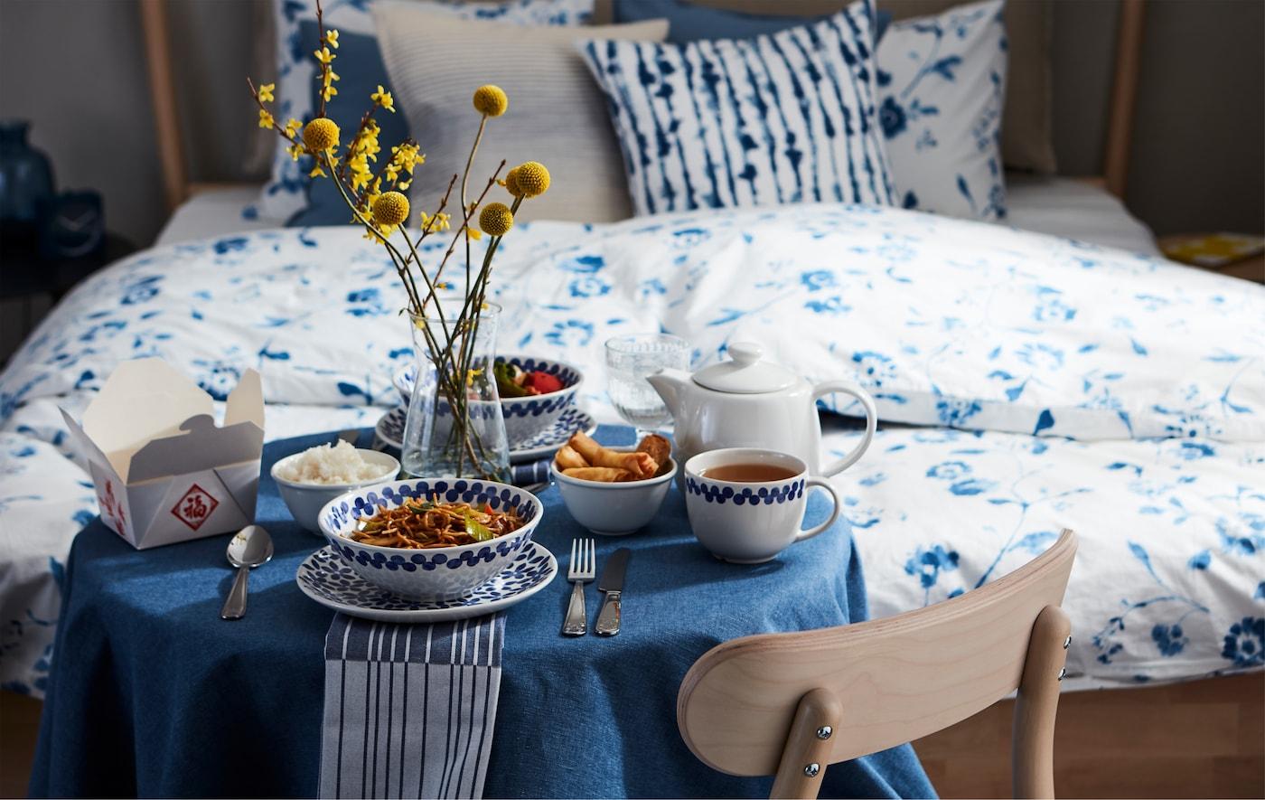 Mesa posta cuidadosamente para um jantar a sós com comida entregue em casa, saboreado junto à cama para parecer um serviço de quartos.