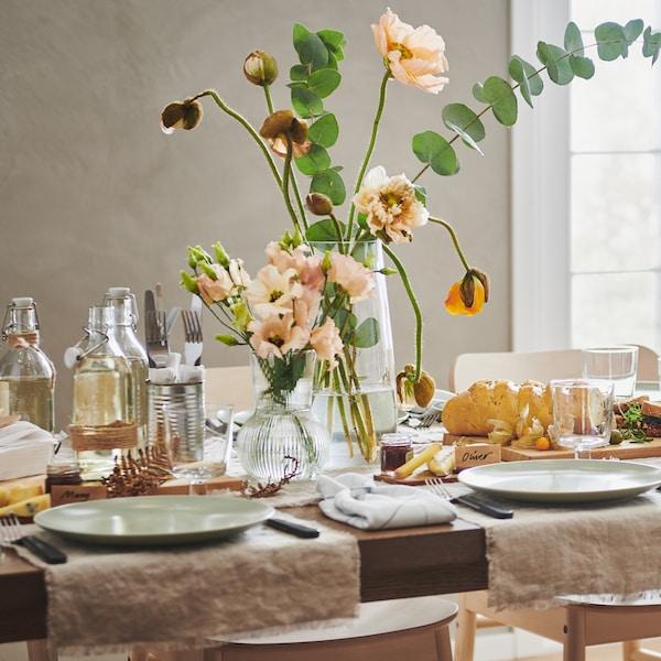 Mesa posta para uma refeição com tons neutros e loiça em verde claro. Jarra de flores, comida e garrafas em cima da mesa.
