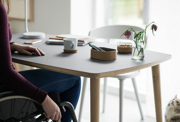 Mesa resistente a los arañazos OMTÄNKSAM con suficiente espacio para las piernas para una silla de ruedas diseñada en colaboración con expertos en ergonomía.