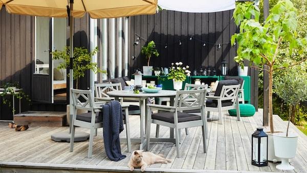 Mesa y sillas BONDHOLMEN en un jardín exterior