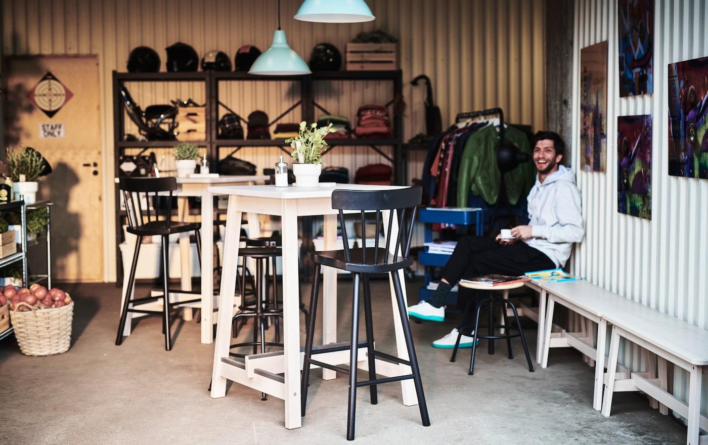 Mesas altas e bancos altos com encosto NORRÅKER, em madeira clara, numa pequena quinta decorada com ambiente de café.