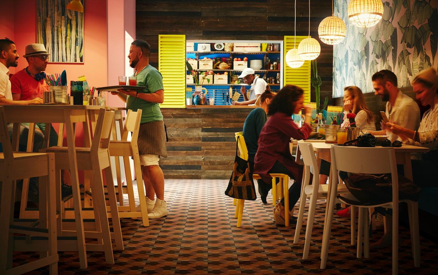 Mesas altas em bétula clara e bancos altos em bétula da gama NORRÅKER, num restaurante pequeno com candeeiros suspensos INDUSTRIELL em bambu.