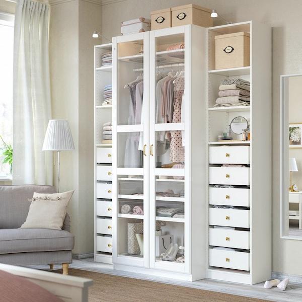 Messingfarvede greb og knopper på en hvid garderobeskabskombination med glasdøre og åbne hylder.
