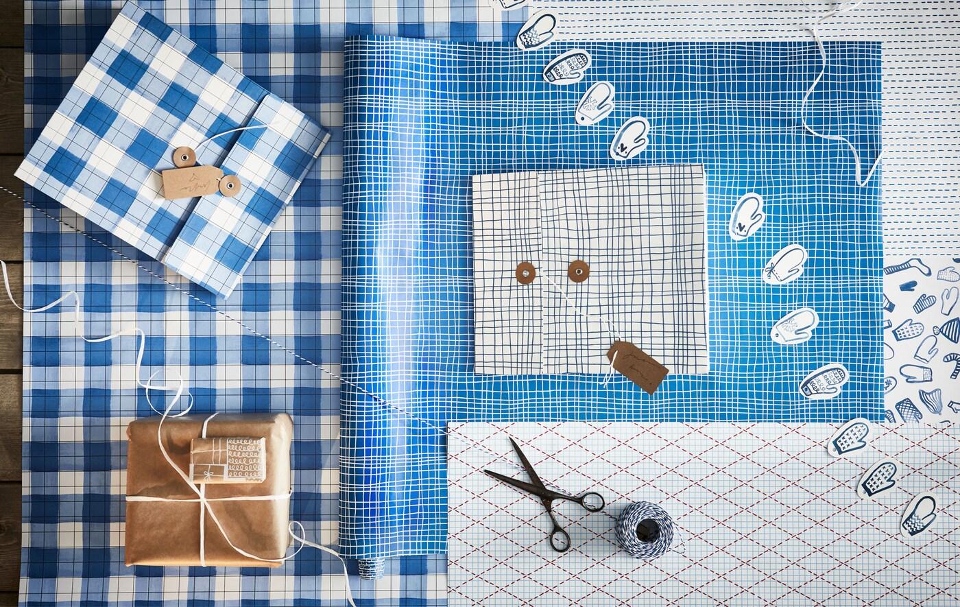 Место для упаковки подарков с обрезками: цветная бумага с различными узорами, веревка, ножницы, этикетки и подарочные коробки.