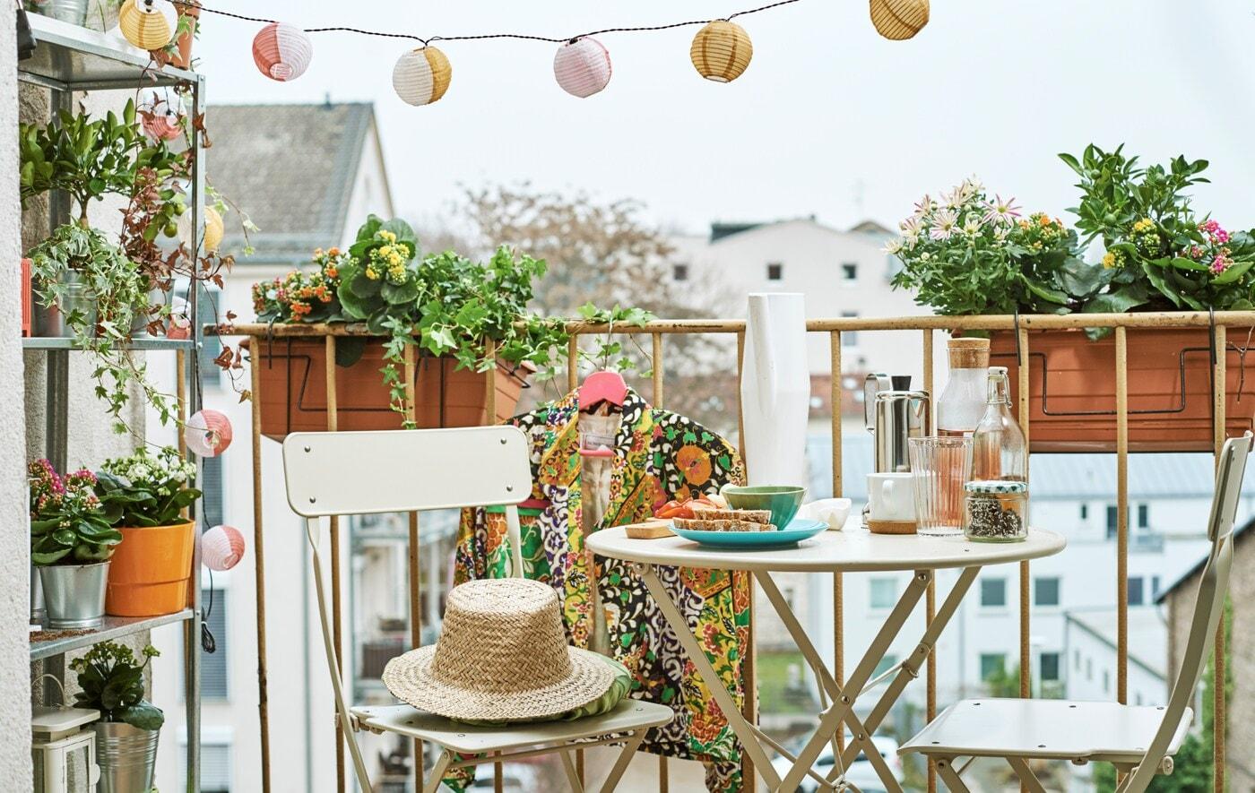 Městský balkon plný truhlíků s květinami, policovým dílem plným květin, venkovním osvětlením a stolkem s židlemi