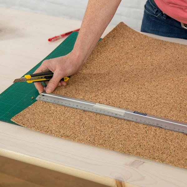 Mesurez la largeur et la longueur de la surface supérieure et coupez le liège sur un rouleau (chez Brico) en fonction de ces mesures à l'aide d'un briseur et d'une barre métallique.