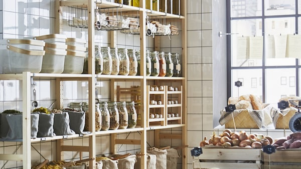 Metal bottle pantry shelving unit in a kitchen with white subway tiles.