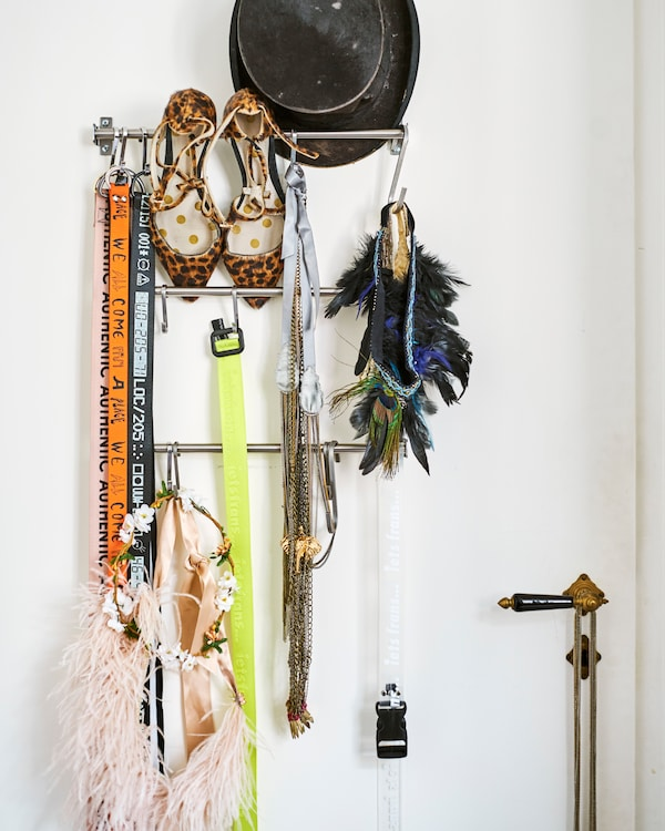 Metal kitchen rails on a white door store accessories including a top hat, leopard-print heels, necklaces and lanyards.