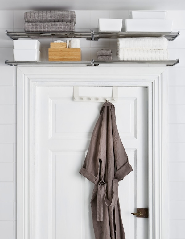 Metal shelves are placed above a door frame and store towels and other extras, while a bathrobe hangs from a door hanger.