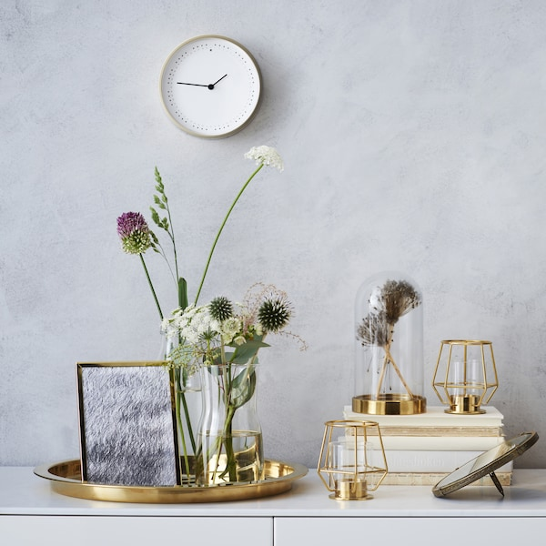 Metallic home accessories and a flower arrangement on top of a white unit.