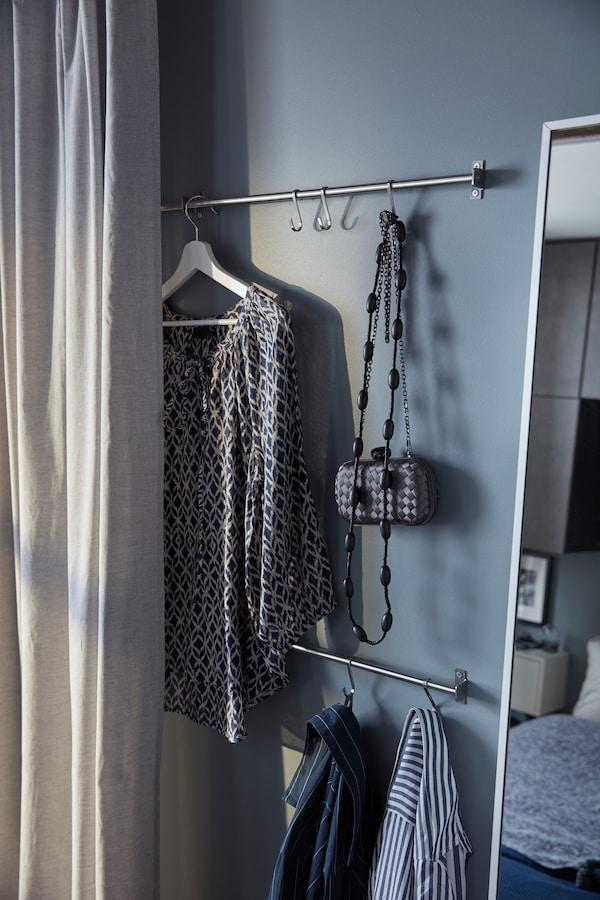 Metalne kuhinjske šine na belim vratima služe za odlaganje dodataka, uključujući cilindar, cipele s leopardovim printom, ogrlice i kaišići.