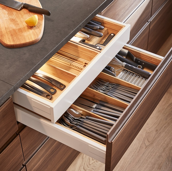 METOD أدراج مطبخ من ايكيا، مفتوحة مع أدوات تناول طعام منظّمة في ملحقات أدراج وإضاءة مثبتة في الداخل.