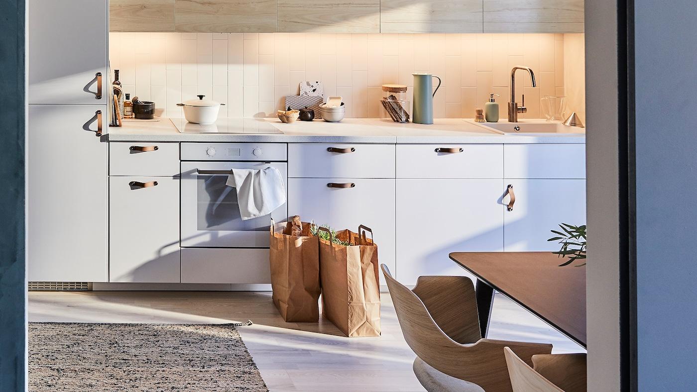 METOD-kjøkken med lyse fronter med askemønster og et flatvevd teppe laget av jute og ull.