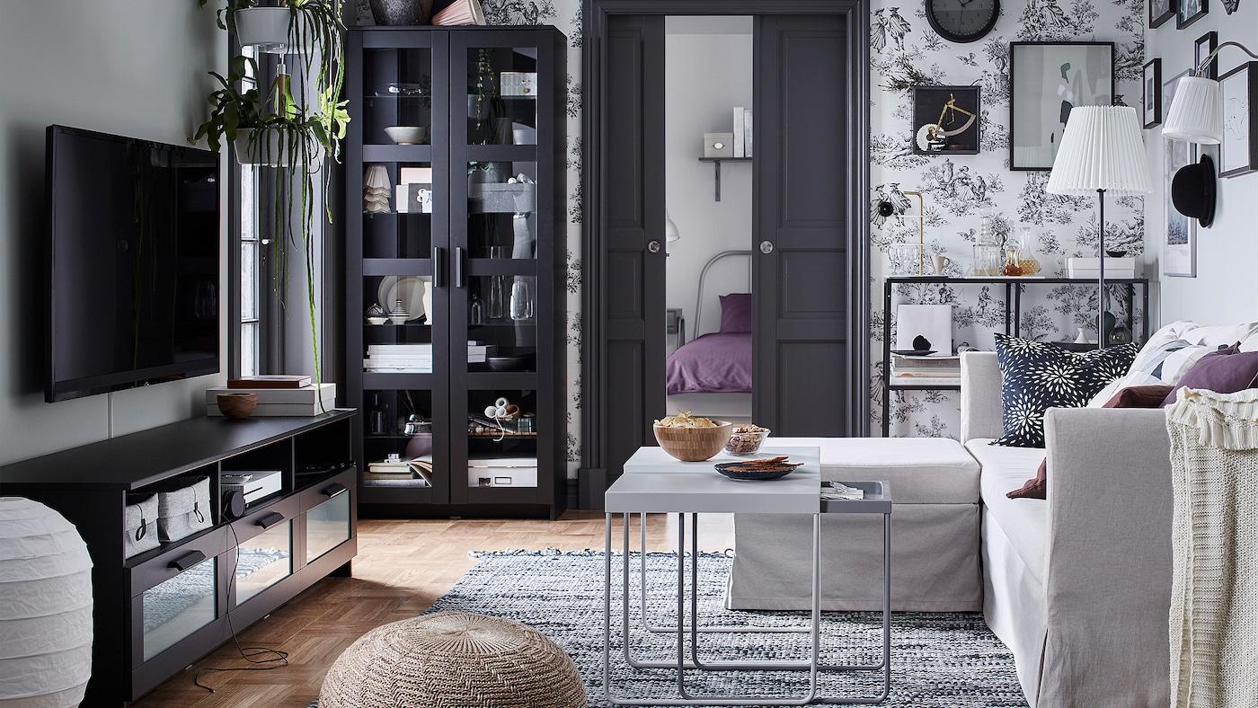 Meuble TV et armoire IKEA BRIMNES noirs en face d'un canapé beige SANDBACKEN dans un séjour.