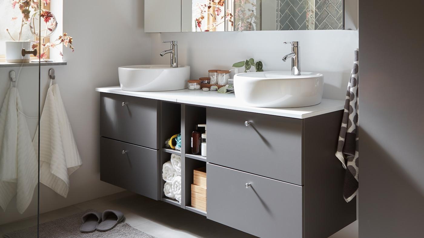 Meubles de salle de bains gris GODMORGON/TOLKEN avec quatre tiroirs de rangement dissimulés et quatre compartiments de rangement ouverts.