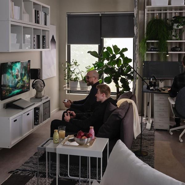 Męzczyzna grający z synem na telewizorze  w pokoju dziennym z półkami serii KALLAX.